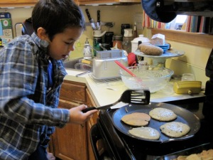 Ben, age 7, flipping blueberry pancakes.